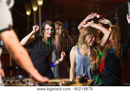 Happy friends dancing by the dj booth at the nightclub