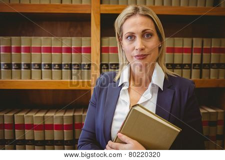 Portrait of a librarian posing and holding a book in library