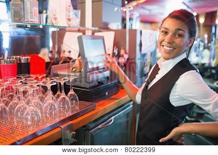 Pretty barmaid using touchscreen till in a bar