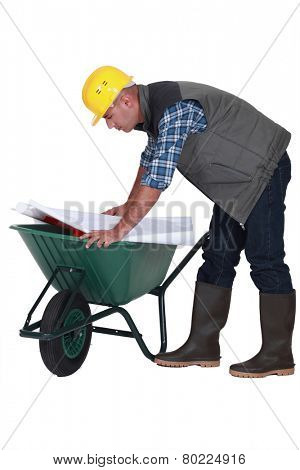 Tradesman looking at a blueprint while leaning over a wheelbarrow