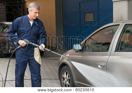 Closeup Of A Mature Man Washing A Car By Pressured Water At Service Station