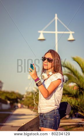 Young girl with skateboard and headphones looking smartphone