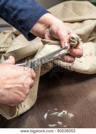 Closeup of senior woman's hands trimming linen border using scissors