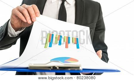 Businessman Analysing A Set Of Graphs And Holding A Map With Statistics In His Hand