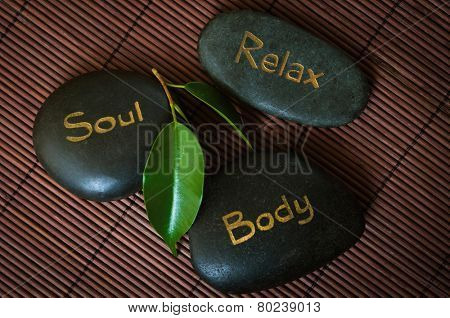 Three black massage stone with words Body, Soul and Relax