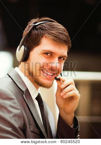 young man working at callcenter using headset