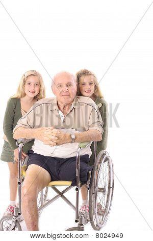 Great grandfather in wheelchair with grandchildren vertical