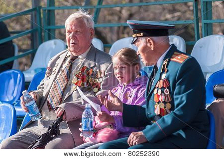 Senior veterans of World War II on tribune