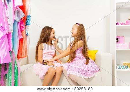 Girl applying make-up on her friend while sitting