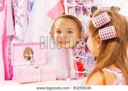 Beautiful small girl reflecting in round mirror