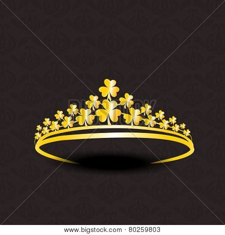 Stylish gold crown decorated by shiny golden shamrock leaves on seamless dark brown background.