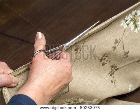 Closeup of senior woman's hands cutting linen in half using scissors