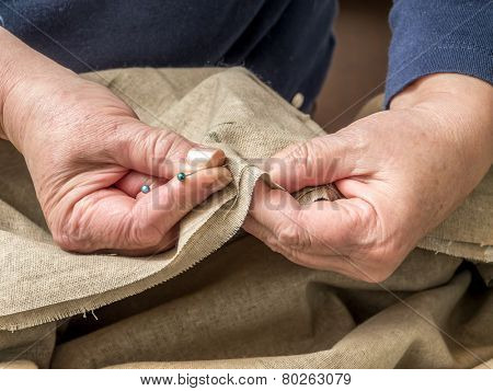 Closeup of senior woman's hands basting linen border using pins