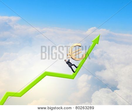 Young businessman rolling up the hill big euro sign