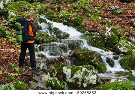 Photographer taking pictures of a mountain river