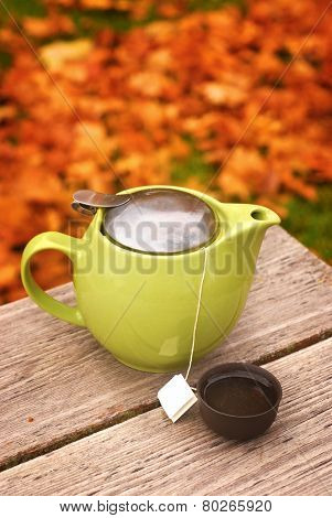Tea pot with cup on autumn table