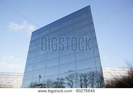 Facades Of Modern Glass Building With Reflections Of Blue Sky And Trees