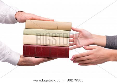 Hands passing heap of books