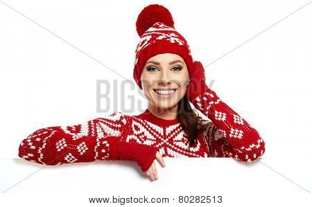 Winter girl happy smile hold sale poster, attractive young excited woman wear warm wool sweater red hat, blank board isolated over white background
