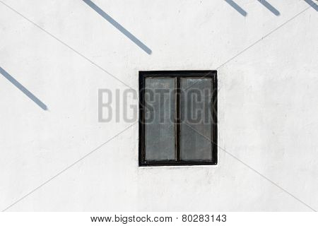 Window on white wall and poles shadow