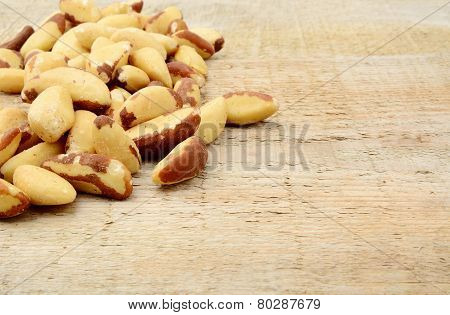 Brasil Nuts In The Corner On Wooden Plank