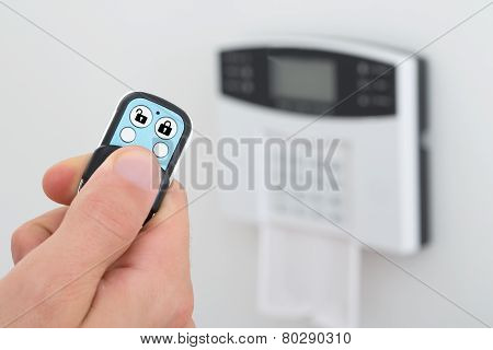 Close-up Of A Person Using Security Alarm Remote Control