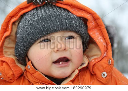 Portrait Of Smiling Baby With Snow In Winter Clothes