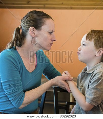 Mother and her 6 year-old son having a difference of opinion, with mother grabbing his hand