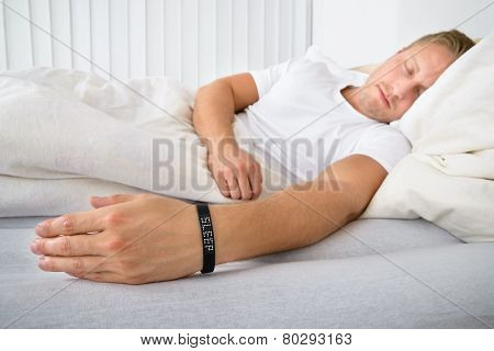 Young Man Sleeping Wearing Smart Wristband