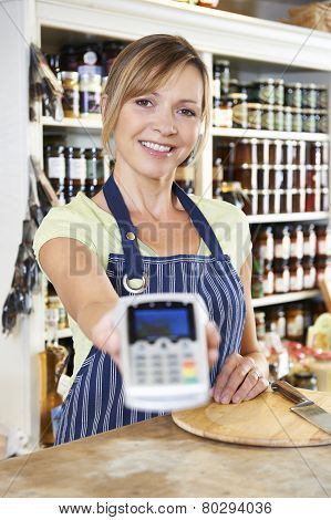 Sales Assistant In Food Store Handing Credit Card Machine To Customer