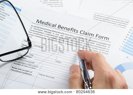 Hand With Pen Over Medical Claim Application