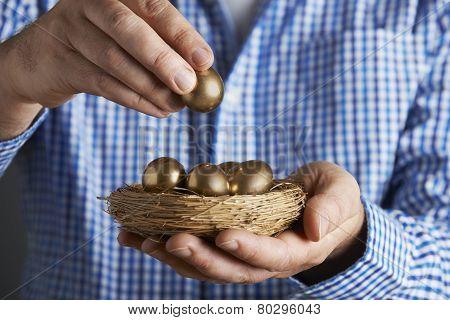 Man Holding Nest Full Of Golden Eggs