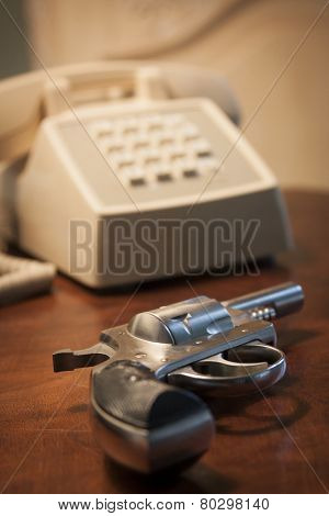 A close-up of a .32 caliber pistol next to a telephone on a brown wooden nightstand table, shallow depth of field.