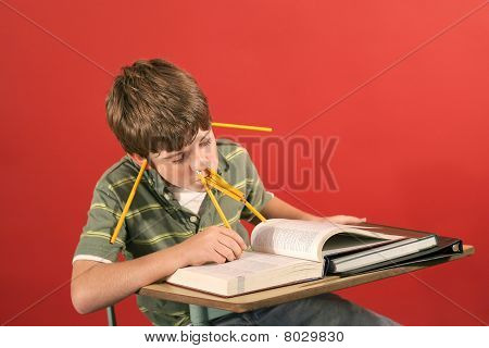 goofy kid studying with pencils