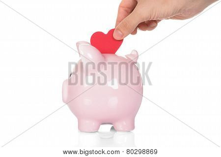 Hand Deposit Red Heart In Piggy Bank