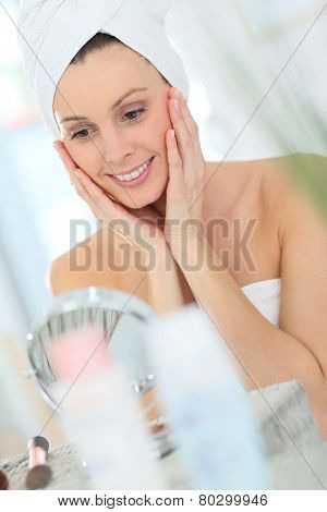 Beautiful woman applying moisturizing cream on her face