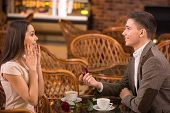 picture of propose  - Man is making proposal with the ring to his girlfriend at the restaurant - JPG