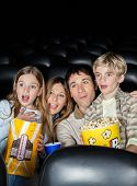 stock photo of watching movie  - Surprised family of four with popcorn watching movie in cinema theater - JPG