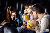 picture of silence  - Family showing silence gesture to woman using mobilephone in cinema theater - JPG