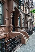 image of brownstone  - Old apartment buildings with fire escapes on the West side of Manhattan - JPG