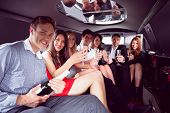 stock photo of alcoholic drinks  - Happy friends drinking champagne in limousine on a night out - JPG