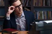 stock photo of typewriter  - Thoughtful young author working at the typewriter and adjusting his eyeglasses while sitting at his working place with bookshelf in the background - JPG