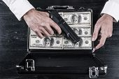 picture of top-gun  - Top view of man holding gun and opening a briefcase full of paper currency - JPG