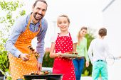foto of tong  - Father and daughter barbecue meat spits and sausages at family garden BBQ  - JPG