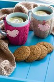 picture of blanket snow  - Two blue cup of tea in knitted sweater with hearts felt standing next to tangle bright filaments and blanket knitted on blue background - JPG
