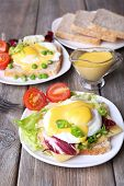 image of benediction  - Toast with egg Benedict and tomato on plate on wooden table - JPG