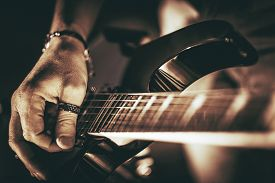 picture of string instrument  - Guitarist Plays - JPG