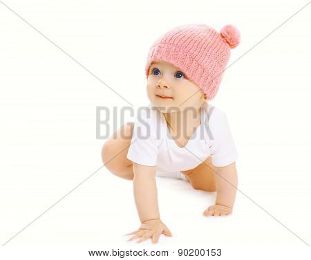 Portrait Of Sweet Baby Crawls In The Pink Knitted Hat And Looking Up