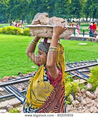 female worker carries rock waste on her hat