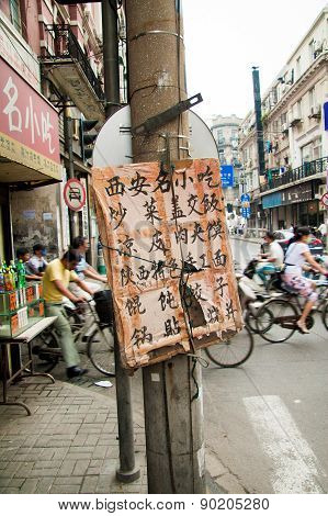 Pancard With Chinese Characters And Bicycles Passing By In The Old Center Of Shanghai, China